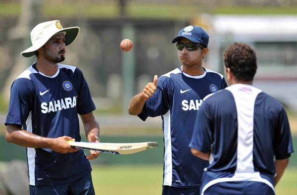 ... chat during a practice session. (Photo by LAKRUWAN WANNIARACHCHI/AFP