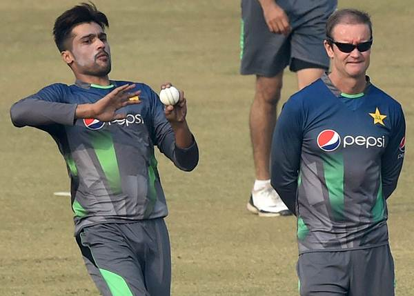 Pakistan cricket batting coach Grant Flower (R) watches as cricketer Mohammad Amir bowls during a team practice session at a camp ahead of the New Zealand tour, in Lahore on January 2, 2016. Paceman Mohammad Amir, who served a prison term for spot-fixing, said he was ready to respond to his critics with wickets -- and love -- after being selected for Pakistan's limited-overs tour of New Zealand. AFP PHOTO / Arif ALI / AFP / Arif Ali (Photo credit should read ARIF ALI/AFP/Getty Images)