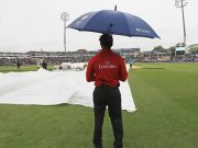 Umpire Kumar Dharmasena looks on, as rain stops play during the ICC Champions Trophy
